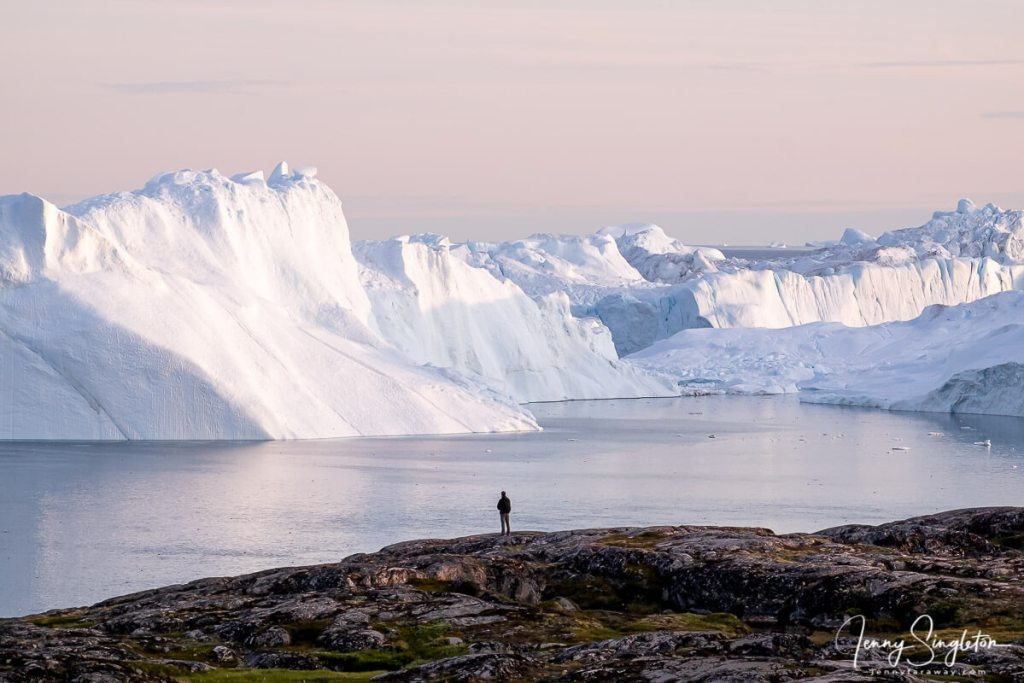 A man stands on the coast overlooking the giant icebergs of the Ilulissat Icefjord, Greenland