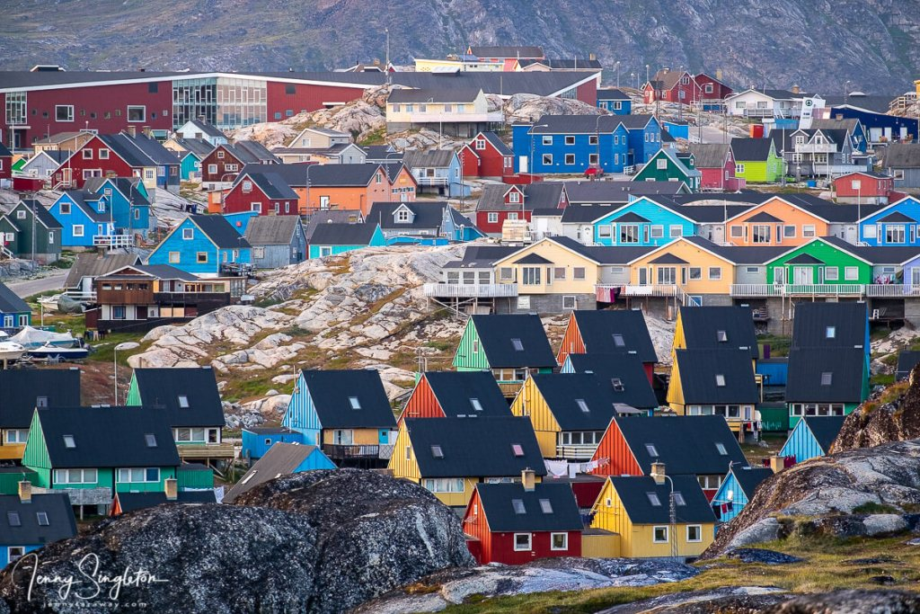 The colourful houses of Ilulissat rise on a hillside, as seen from the Yellow Trail