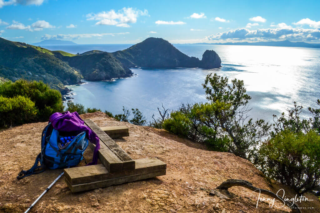 A bench and my bag at a viewpoint overlooking the ocean and a headland on the Coromandel Track, New Zealand