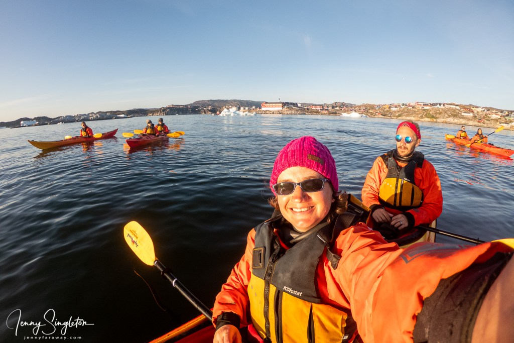 I take a selfie with me and my kayak partner behind me, in front of the town of Ilulissat