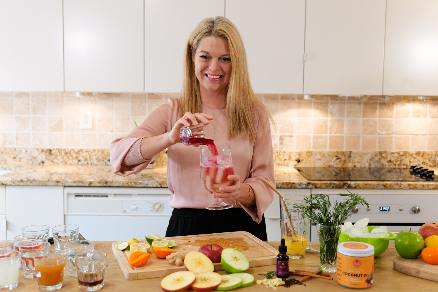 Jenny pouring a red colored drink in her kitchen with a spread of fruits on the counter in front of her