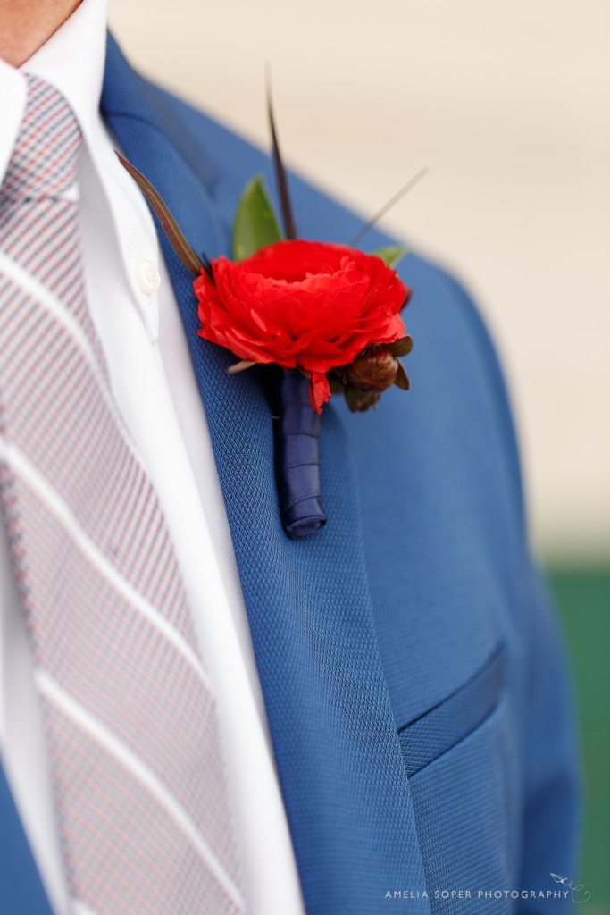 Red ranunculus boutonniere by Jen's Blossoms