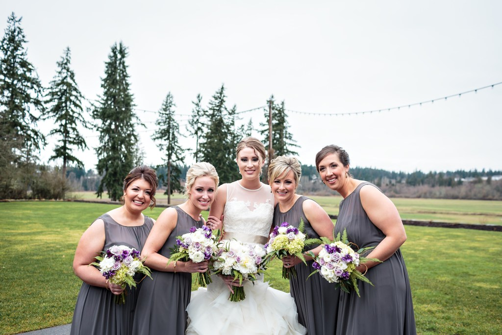 Bridesmaids in charcoal grey dresses carried bouquets of white, purple, and lavender flowers by Jen's Blossoms