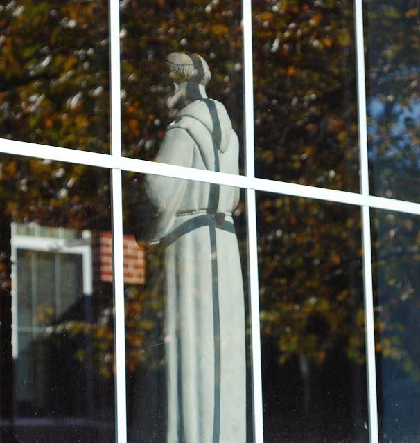 This is the same statue of St. Francis taken from outside. It sits on the ledge of a gymnasium window.