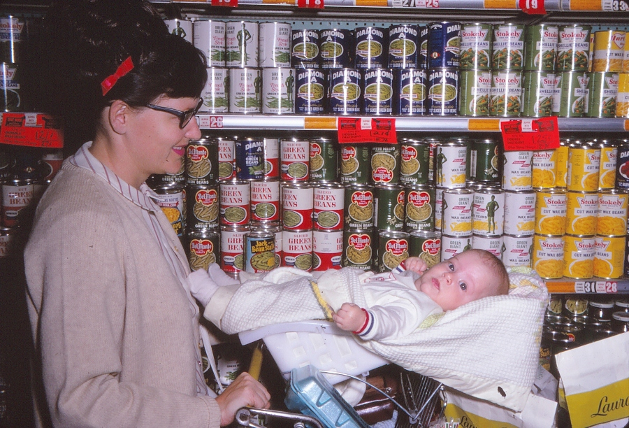 A mother (Silent Generation) pushes a Gen-X baby in a shopping cart. The baby is straddling the flip-up child seat.