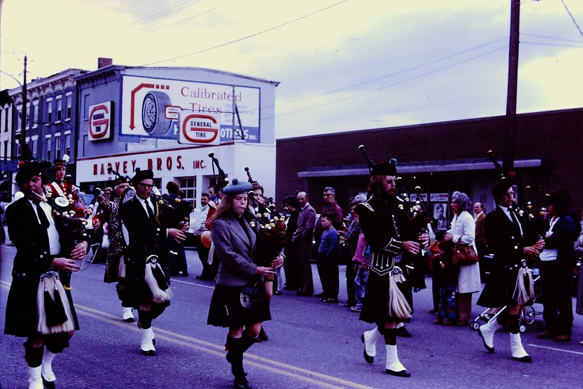 Bagpipers Play march down Main Street America, 1975. Vintage General Tire and Harvey Bros. signs are visible in the background.