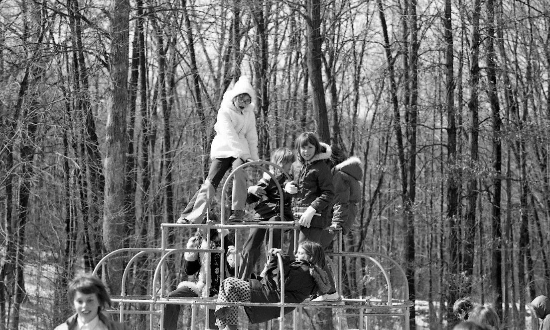 Gen-Xers atop a Jungle Gym 1974