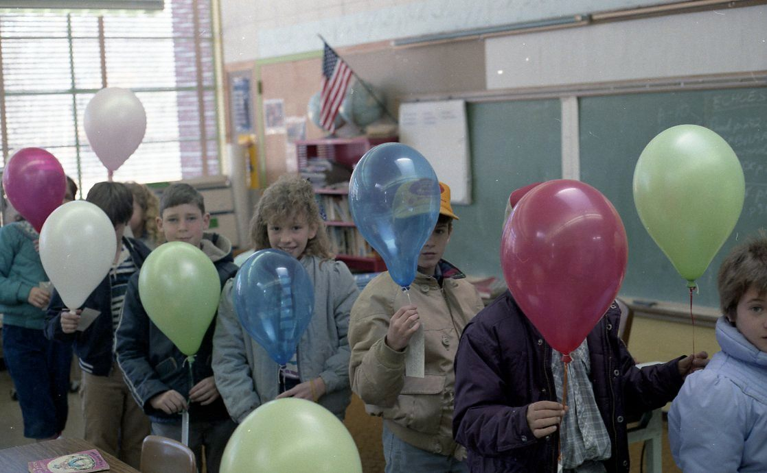 Students line up in a single file before they head outside to release balloons with messages. | Boston Suburb, 1983