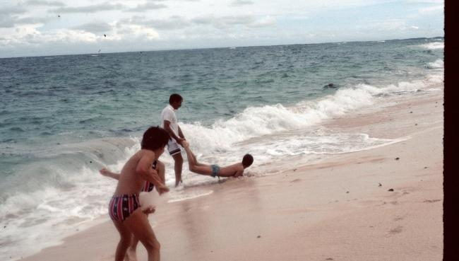 Siblings dragging each other into the ocean 1976