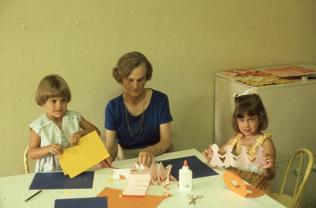 Girls in Sunday School make homemade paper doll garland, 1981