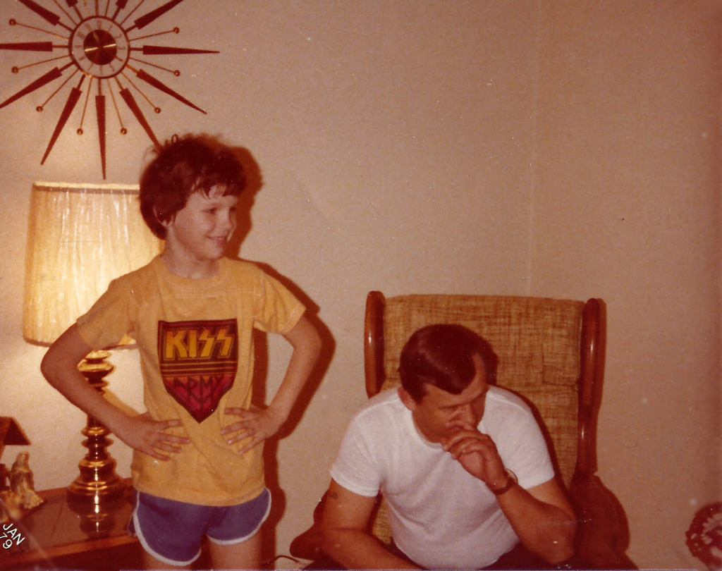 Decades are clashing in this photo of the same kid a KISS concert shirt and the mid-century Pluto clock. It was probably purchased with Green Stamps. LOL.