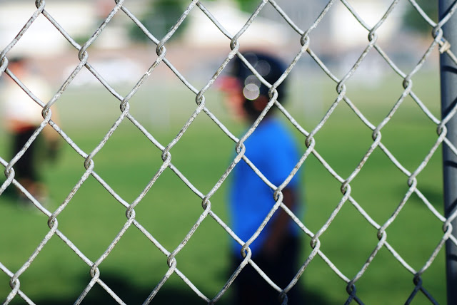 T-ball player though the chain link fence