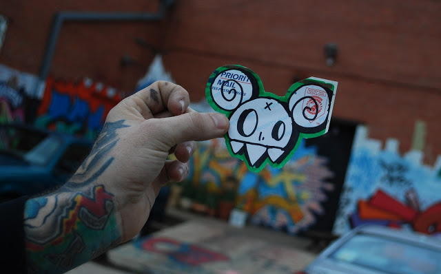 Graff writer holds up his street art sticker.