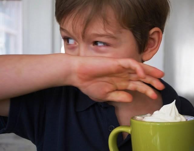 A boy drinking hot chocolate