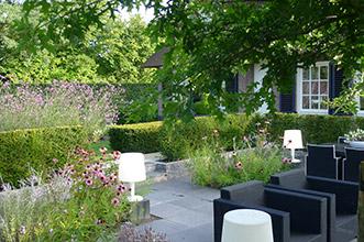 tuinlounge set met buitenverlichting in sfeervol beplante tuin