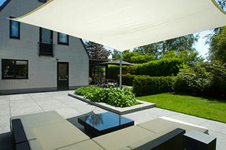 loungebank onder schaduwdoek in moderne tuin