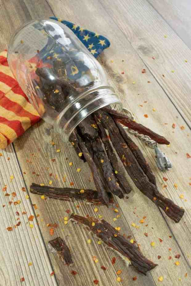 Jerky in a jar laying on wood with red pepper flakes and american flag