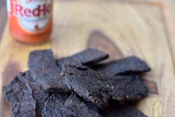 Spicy Jerky with Frank's RedHot finished drying on cutting board with bottle of hot sauce in background