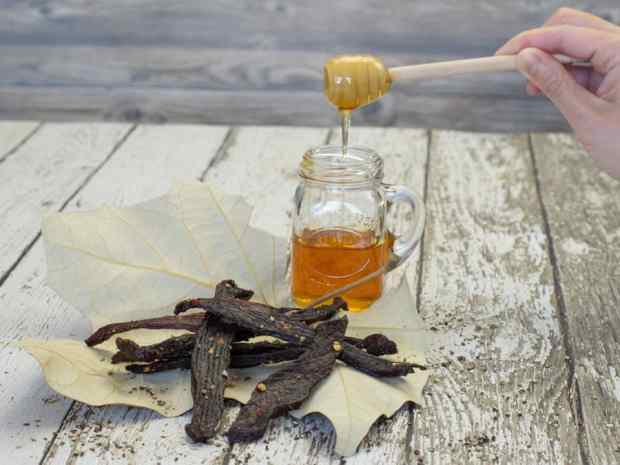 Peppered Honey Deer Jerky finished on wood boards with jar of honey