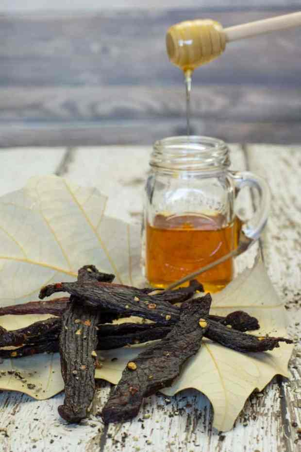 Peppered honey deer jerky on a leaf with a jar of honey with wood background