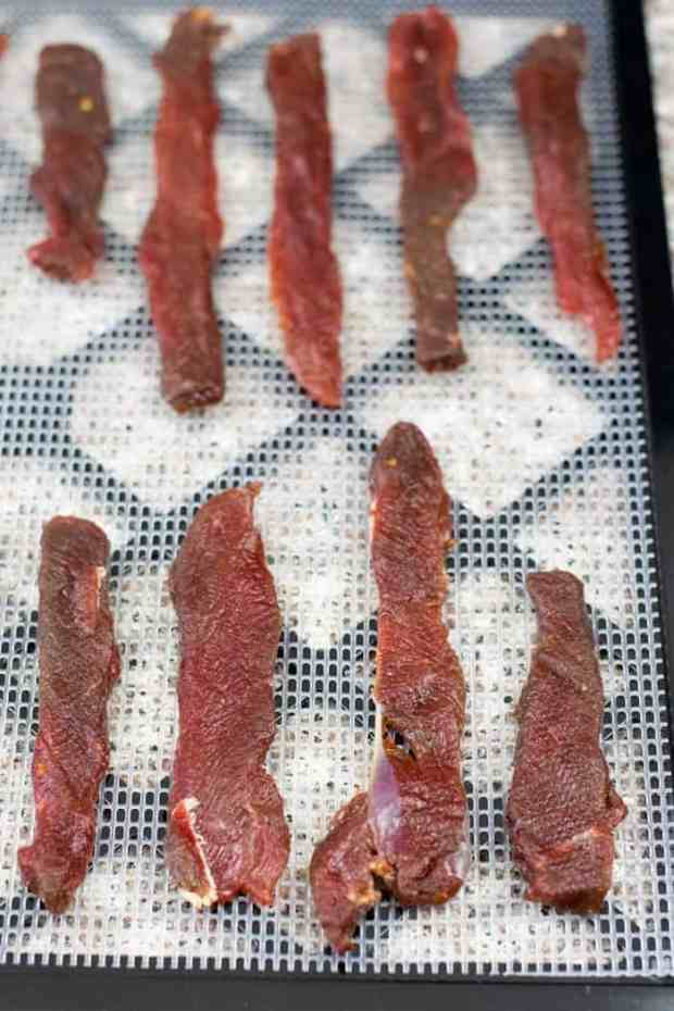 Deer jerky on dehydrator trays ready to be dried