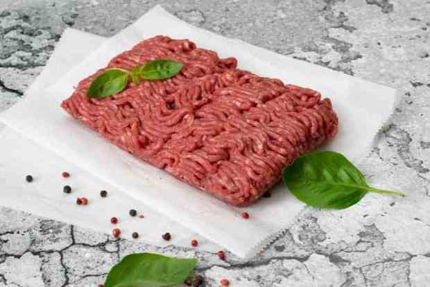 Ground Beef with basil on parchment paper and marble