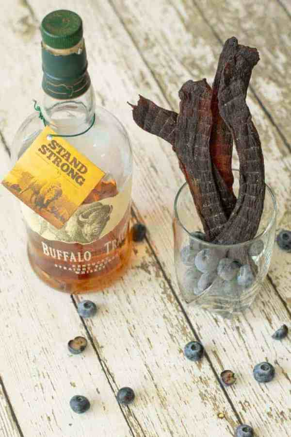 Blueberry deer jerky in a glass full of blueberries on wood table with a bottle of bourbon