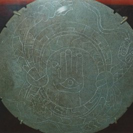 Figure 7. The rattlesnake disc found at Moundville, Alabama. It depicts two knotted snakes surrounding the hand and eye (Ogee) symbol. This disc is interpreted as a depiction of the sky supported by snakes with the hand representing the Orion constellation. The eye, or Ogee, in the palm of the hand probably represents the Orion Nebula viewed by the ancients as the portal through which the souls of the dead passed on their way to the starry pathway, the Milky Way.