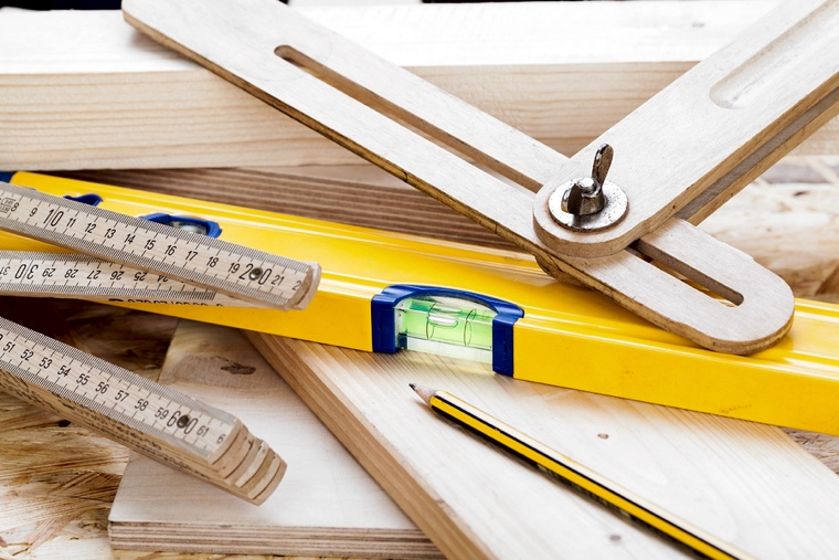 Close up view of a colorful yellow carpenters level ruler and right angle lying on planks of new hardwood together with a pencil for measurements in a carpentry construction DIY and joinery concept