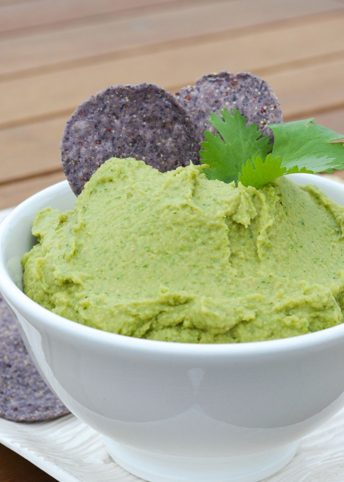 """This Avocado Hummus-- or """"Guacamummus""""-- is the perfect smooth combination of creamy avocado and chick peas. It's lightly spiced with guacamole flavors and the perfect healthy snack paired with veggies or tortilla chips!"""
