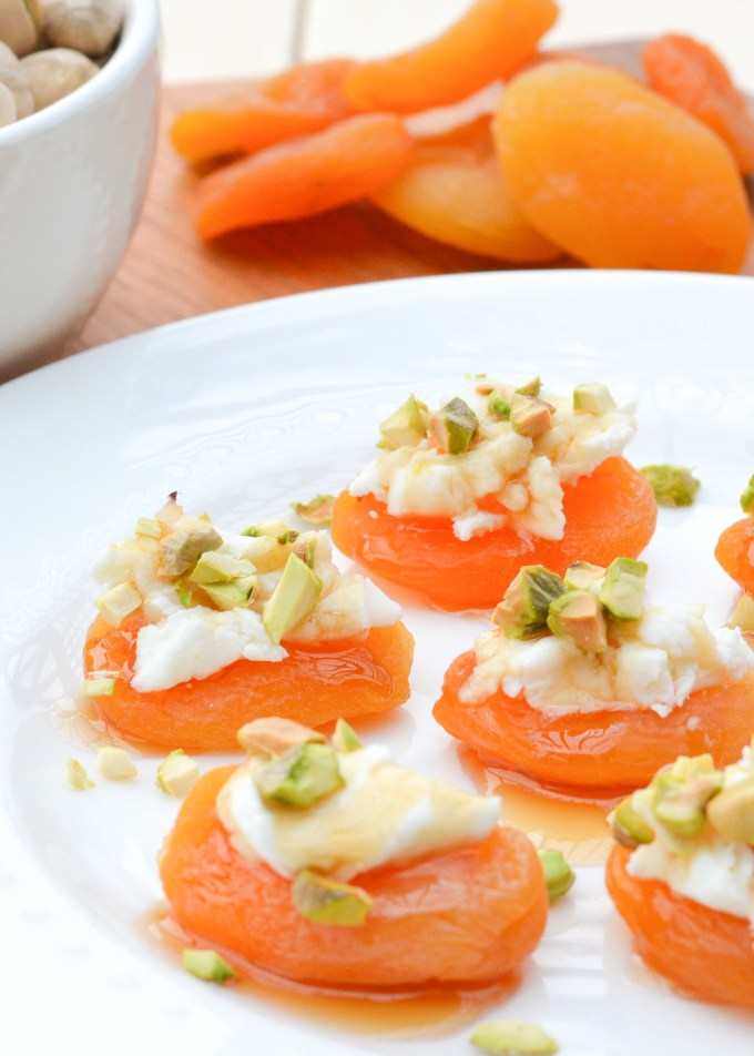 Dried apricots are topped with creamy goat cheese, crunchy pistachios and a drizzle of honey. These Pistachio & Goat Cheese Apricot Bites are a perfect easy snack or appetizer for your next party or game day gathering!