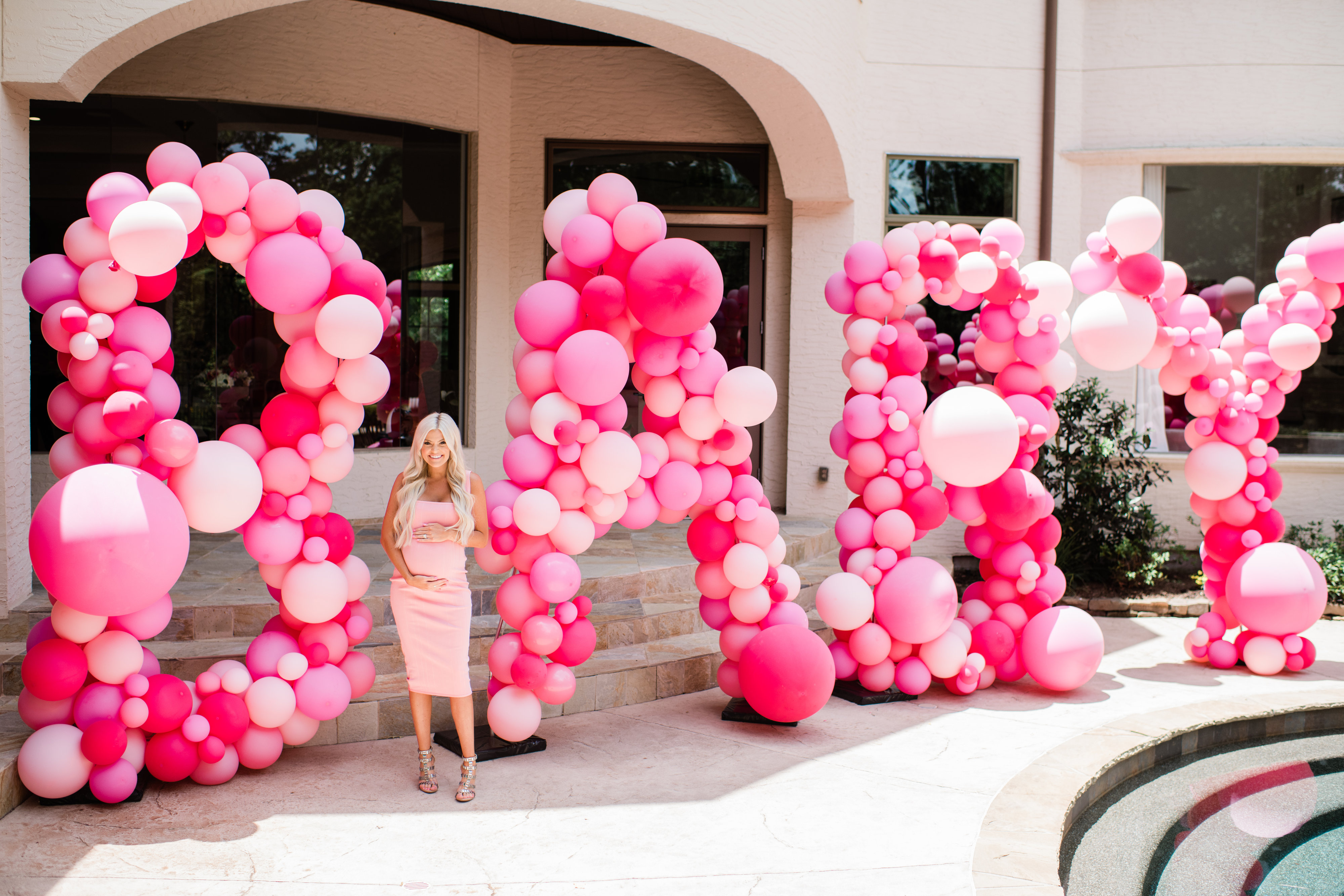 Cute Pink Baby Shower Ideas featured by top Houston lifestyle blogger and expecting mom, Jessica Crum. | Pink Baby Shower by popular Houston motherhood blogger, Jessica Crum: image of Jessica Crum wearing a pink dress and standing in front of a baby pink balloon sign.