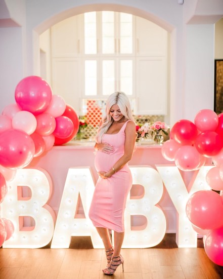 Cute Pink Baby Shower Ideas featured by top Houston lifestyle blogger and expecting mom, Jessica Crum. | Pink Baby Shower by popular Houston motherhood blogger, Jessica Crum: image of Jessica Crum standing in front of a Alpha Lit Austin baby marquis sign.