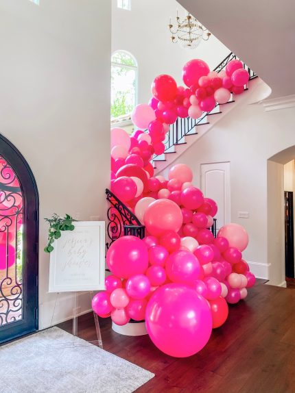 Cute Pink Baby Shower Ideas featured by top Houston lifestyle blogger and expecting mom, Jessica Crum. | Pink Baby Shower by popular Houston motherhood blogger, Jessica Crum: image of a Lushra pink balloon garland on a stair case.