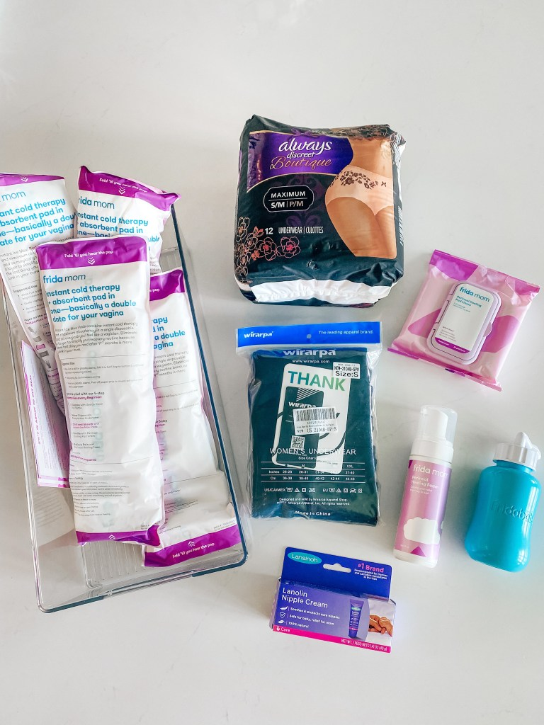 Hospital Bag by popular Houston motherhood blogger, Jessica Crum: image of a acrylic storage bin containing a Frida Mom Perineal Medicated Witch Hazel Healing Foam for Postpartum Care, Lansinoh Lanolin Nipple Cream for Breastfeeding, Always Discreet Boutique Incontinence & Postpartum Underwear for Women, and Frida Mom 2-in-1 Postpartum Absorbent Frida Mom Postpartum Perineal Ice Maxi Pads.