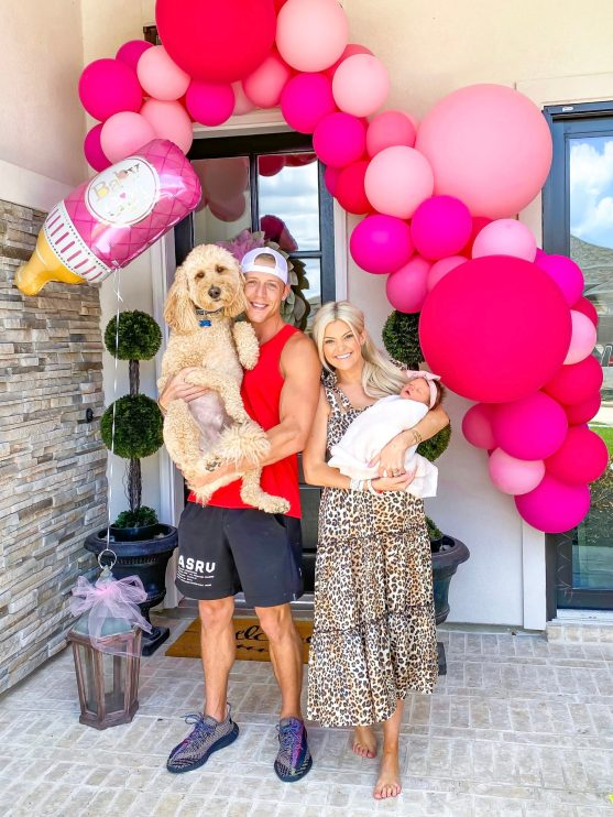 DIY Balloon Garland by popular by Houston lifestyle blog, Jessica Crum: image of Jessica Crum and her husband standing in front of a pink Lushra DIY balloon garland while holding their dog and their new born baby daughter Brynnleigh.