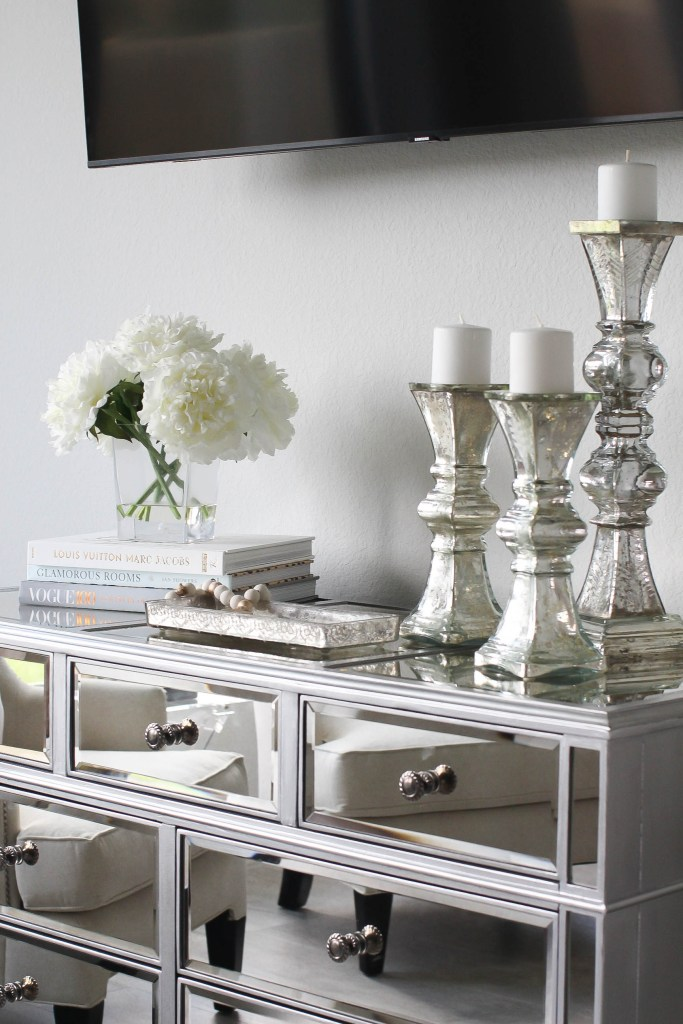 Master Bedroom Ideas by popular Houston life and style blogger, Jessica Crum: image of a Arhaus reese wide dresser with a set of silver candlestick holders, and CB2 ATHENA RIBBED GLASS TANK TRAY.