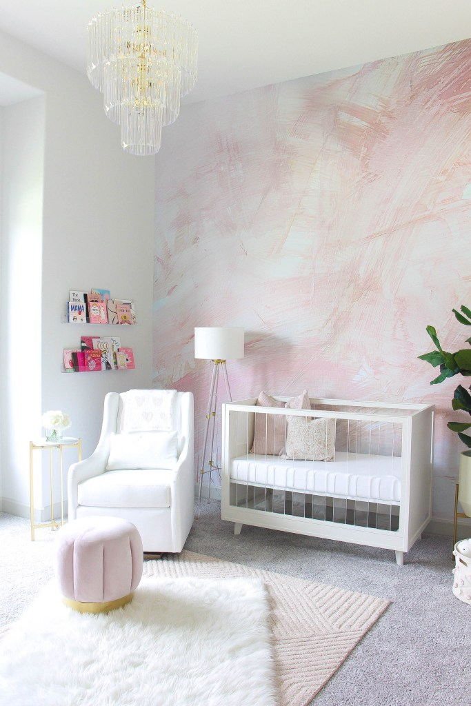 Girl Nursery by popular Houston motherhood blogger, Jessica Crum: image of a nursery decorated with Wall Blush The Nora Mural, Pottery Barn Kids  Sloan Acrylic Convertible Crib, Barefoot Dreams Cozychic Dream Receiving Blanket, Target tufted ottoman, acrylic floor lamp, crystal chandelier, Pottery Barn Kids Faye Rug, Pehr Pom Pom Bundle, World Market Faux Fiddle-Leaf Fig Plant, World Market Tapered Ivory Planter With Gold Stand, Walmart Burt's Bees Baby Solid Organic Crib Sheet, white glider chair, and Lam Bespoke throw pillows