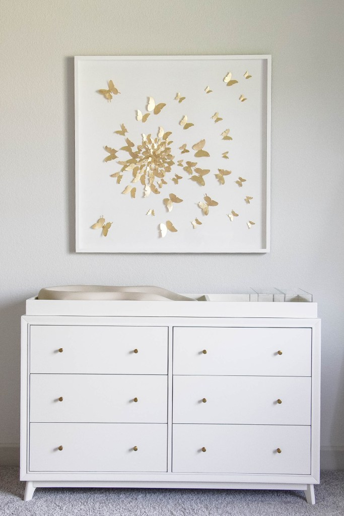 Girl Nursery by popular Houston motherhood blogger, Jessica Crum: image of a nursery decorated with a Pottery Barn Kids Sloan Extra Wide Dresser & Topper, RH Baby & Child HAND-FOLDED PAPER BUTTERFLY SPIRAL ART, Amazon Keekaroo Peanut Diaper Changer, Pottery Barn Acrylic and Metallic Nursery Storage.