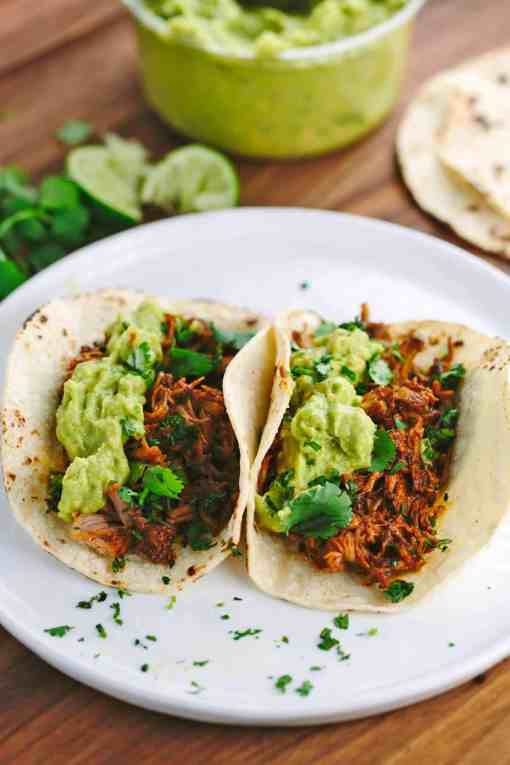 Slow Cooker Mexican Pulled Pork Tacos - Tender pork is simmered in a spicy-sweet mole sauce and filled in warm corn tortillas. | jessicagavin.com
