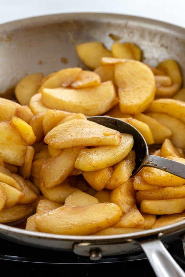 apple slices sautéing in a pan