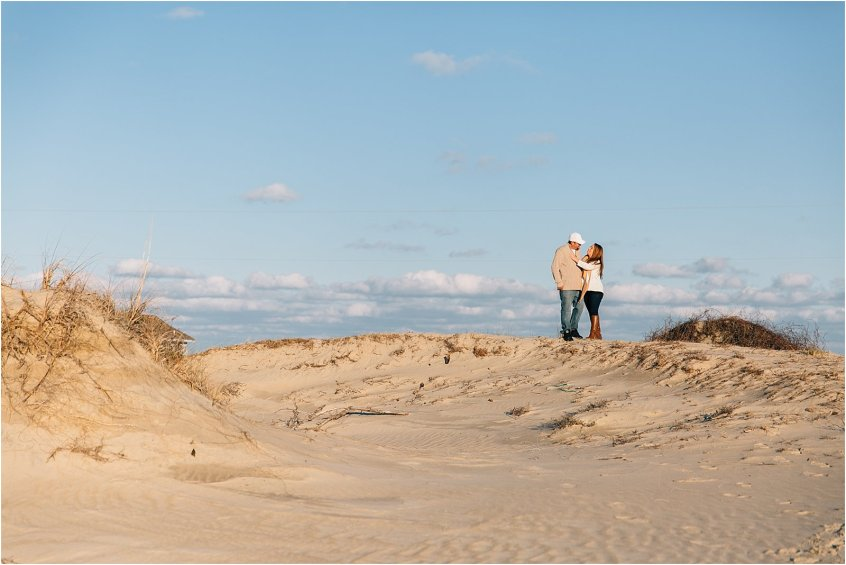 carova beach north carolina engagement portrait wild horses on the beach couple holding hands on sand dune