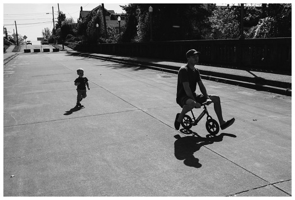 dad on trike while little boy chases him in black and white by Jessica Uhler Photography in Seattle Washington
