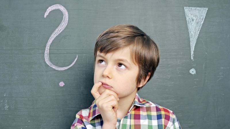 Kind mit Fragezeichen an Schultafel