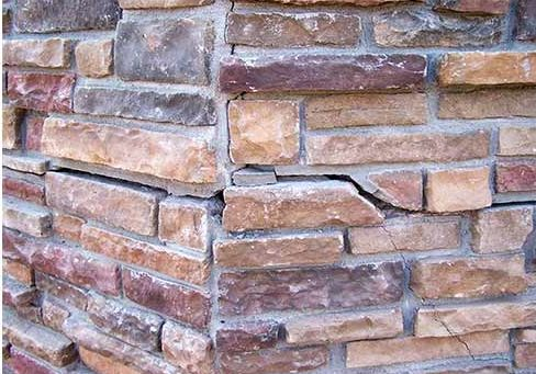 Cracked brick foundation is often caused from shifting soil or foundation settlement