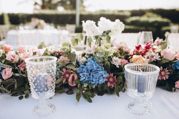 coureur-floral-avec-bougies-bleues-vases-en-verre