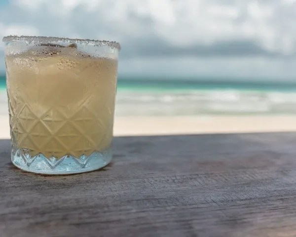 Margarita on a table eat a beach club with the ocean in the background
