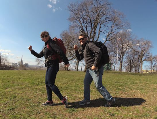 Man and a Woman wearing backpacks walking in sync in a park