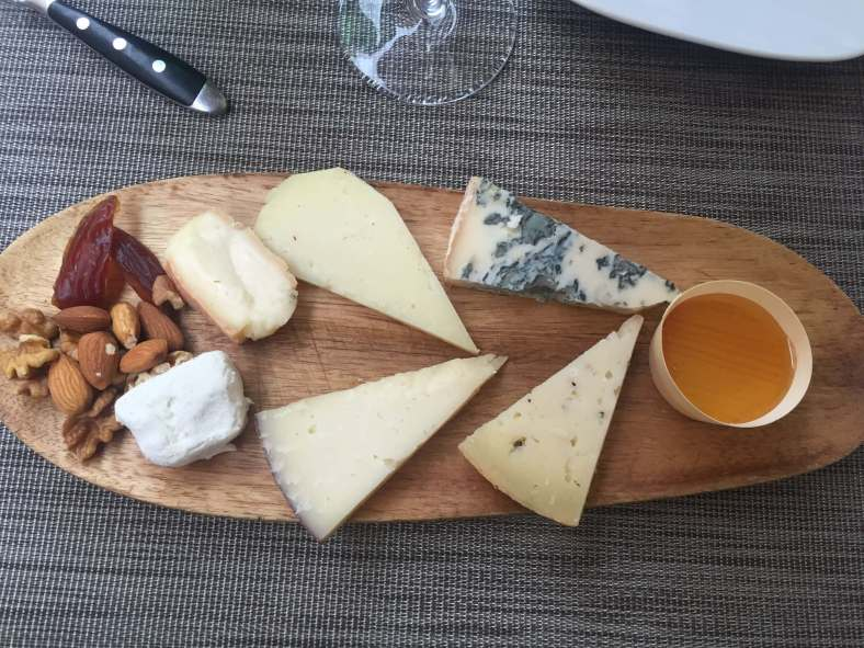 Six different types of cheese on a wooden plate