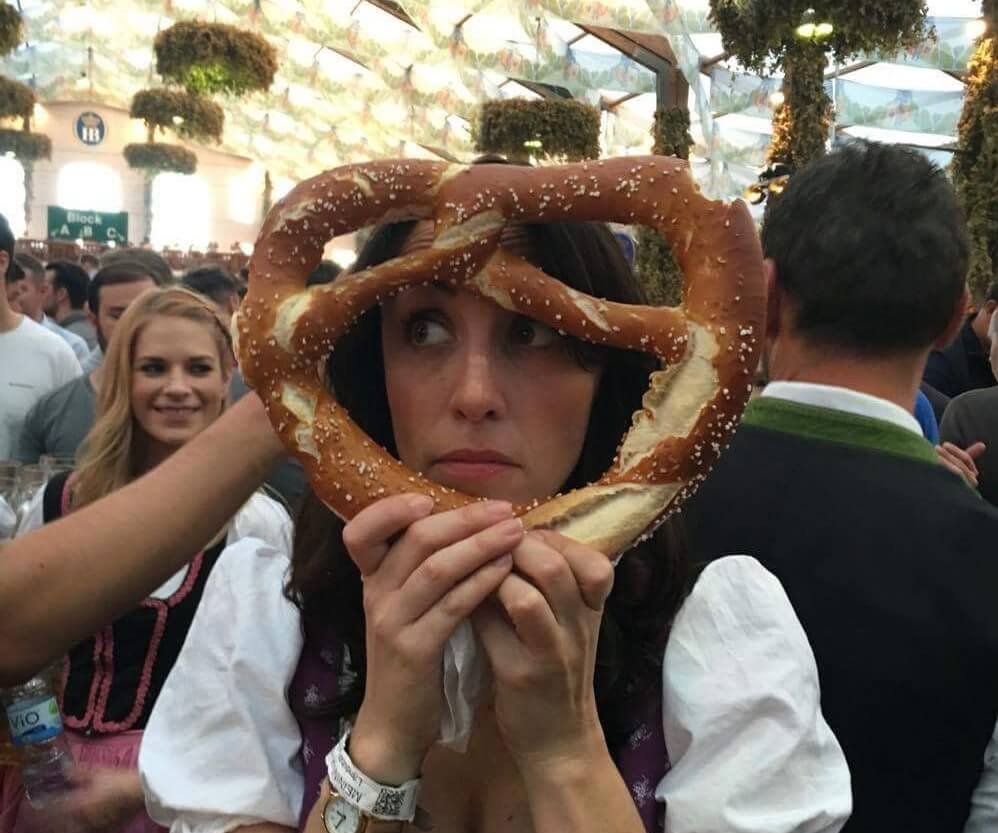 Girl holding a pretzel in front of her face